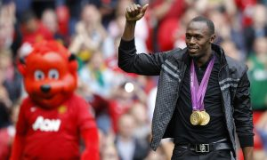 """Jamaican sprinter Usain Bolt, wearing his three gold medals won at the London 2012 Olympic Games, gestures before Manchester United play Fulham in their English Premier League soccer match at Old Trafford in Manchester, northern England, August 25, 2012.  REUTERS/Phil Noble (BRITAIN - Tags: SPORT SOCCER ATHLETICS) FOR EDITORIAL USE ONLY. NOT FOR SALE FOR MARKETING OR ADVERTISING CAMPAIGNS. NO USE WITH UNAUTHORIZED AUDIO, VIDEO, DATA, FIXTURE LISTS, CLUB/LEAGUE LOGOS OR """"LIVE"""" SERVICES. ONLINE IN-MATCH USE LIMITED TO 45 IMAGES, NO VIDEO EMULATION. NO USE IN BETTING, GAMES OR SINGLE CLUB/LEAGUE/PLAYER PUBLICATIONS - RTR3741Q"""